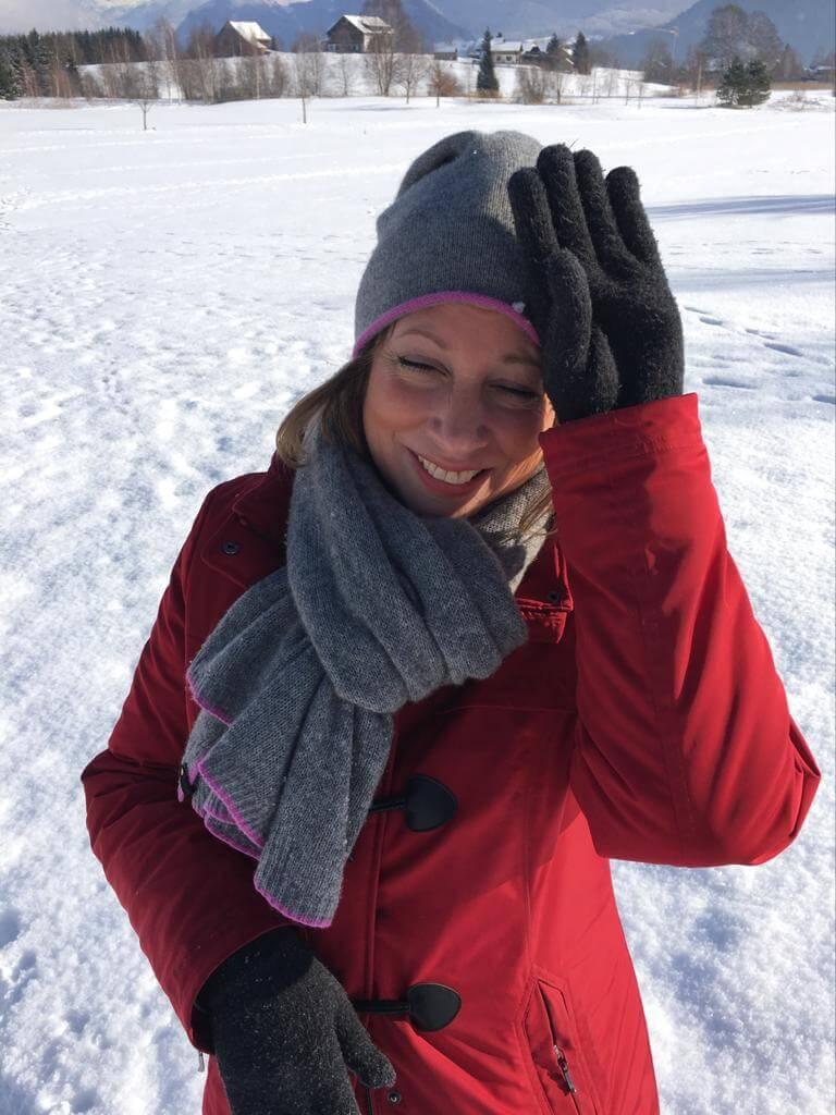 Frau im Schnee-rote Jacke-glücklich-Kinderwunsch-schwanger werden-Coaching-Fehlgeburt-Gedanken-Angst